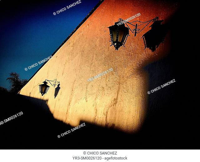 The shadow of a lamp is cast in an orange wall in Tequisquiapan, Queretaro, Mexico