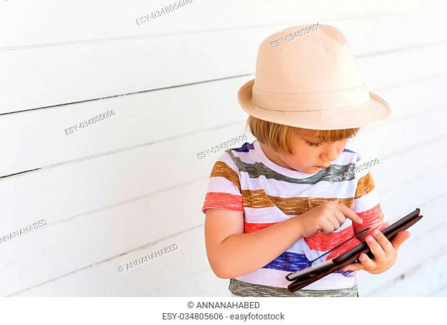 Cute little boy playing with tablet pc wearing a hat, standing against white wooden background