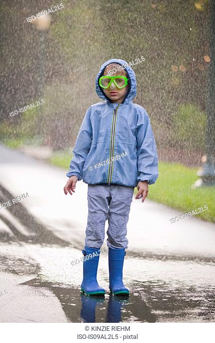 Portrait of boy wearing scuba goggles and rubber boots standing in street puddle