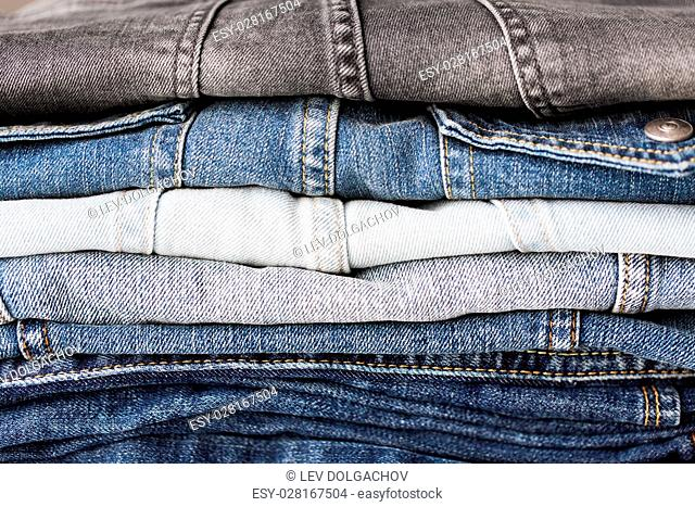 clothes, wear and fashion concept - close up of denim pants or jeans pile