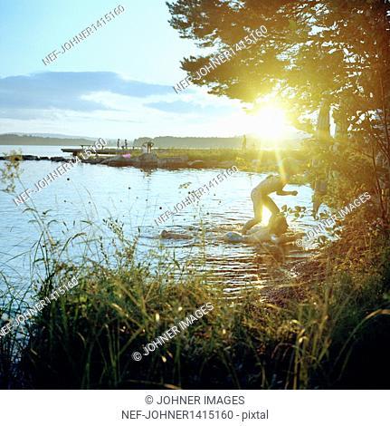 Children playing in lake at sunset