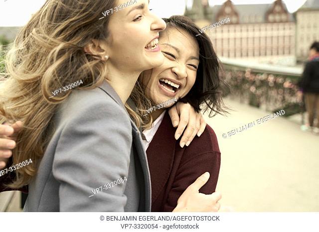 exuberant women embracing each other, in Frankfurt, Germany