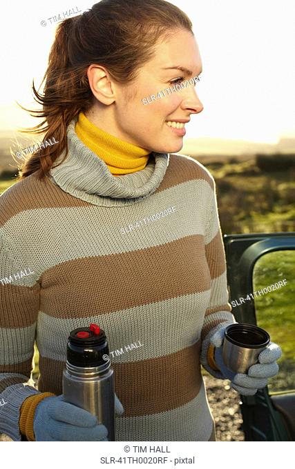 Woman drinking coffee from thermos