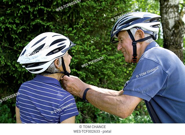 Germany, Bavaria, Senior couple with bicycle helmet, smiling