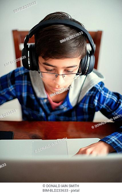 Mixed Race boy listening to laptop with headphones