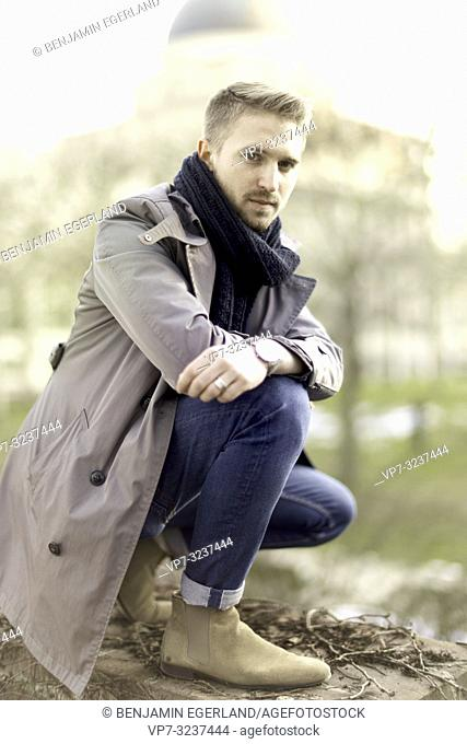 man crouching in city park, in Munich, Germany