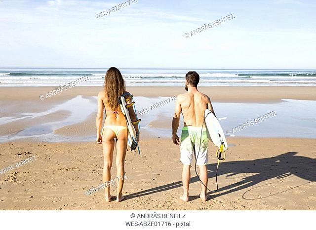Couple carrying surfboards on the beach