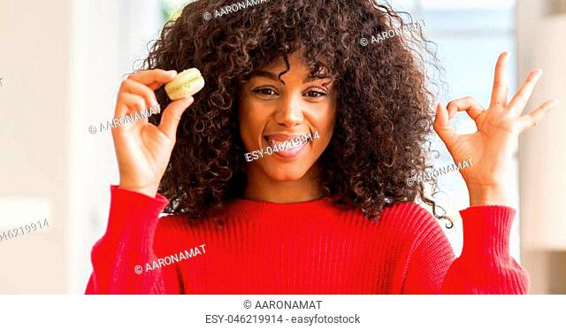 African american woman holding macaron doing ok sign with fingers, excellent symbol