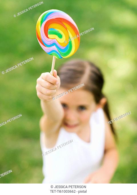Girl (4-5) holding colorful lollipop