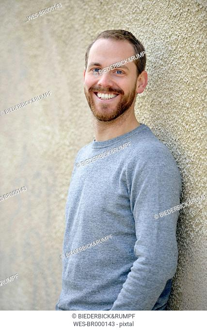 Portrait of relaxed young man leaning at wall