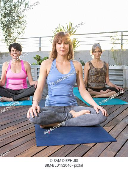 Women sitting on yoga mats on rooftop