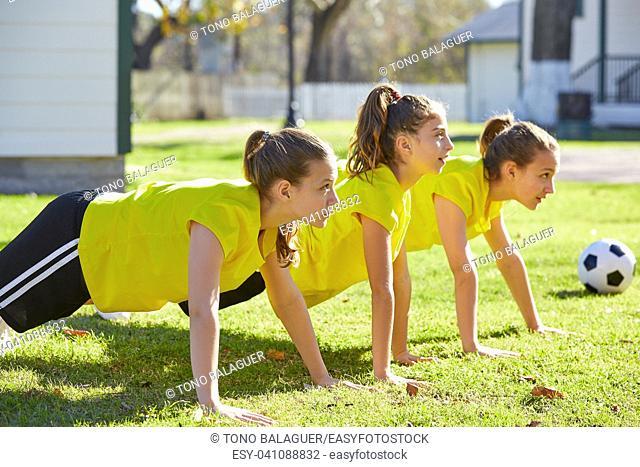 Friend girls teens push up push-ups workout ABS in a park turf grass