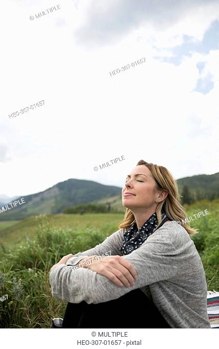 Serene woman relaxing in remote rural field