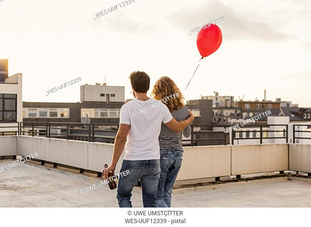 Back view of young couple on roof terrace at evening twilight