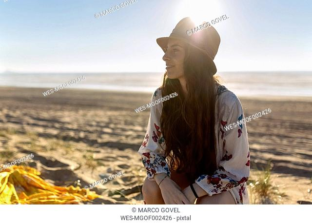 Smiling young woman sitting on the beach at backlight