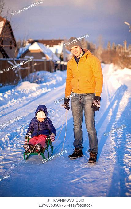 Young dad sledding his little daughter on a sunny winter day