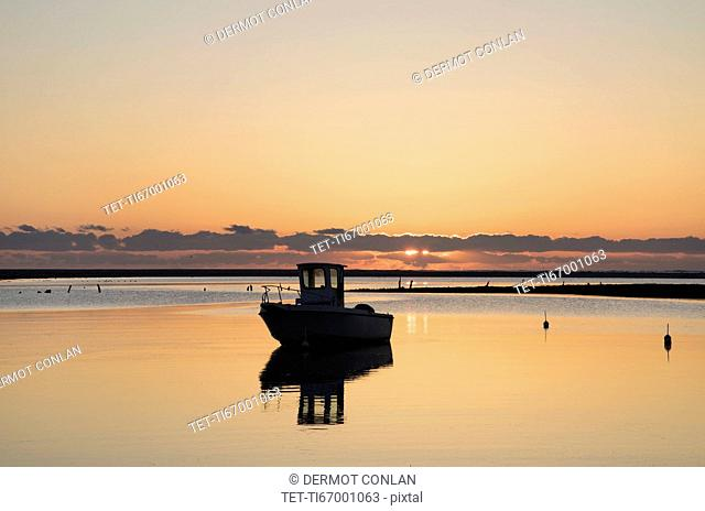USA, Massachusetts, Cape Cod, Chatham, Fishing boat reflecting in water at dawn