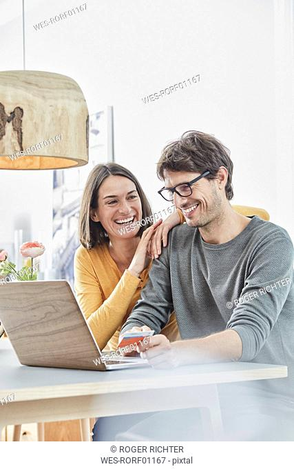 Happy couple with a card using laptop on table at home