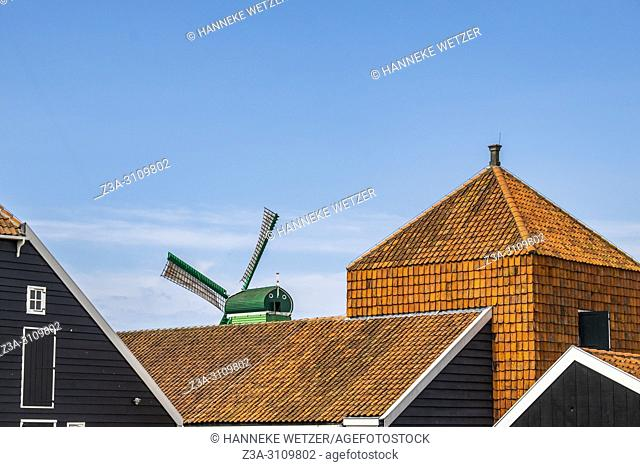 Traditional Dutch windmill behind rooftops at the Zaanse Schans, North-Holland, the Netherlands, Europe