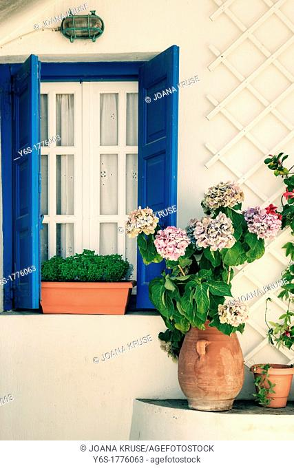a window with blue shutters and flowers, Mykonos, Greece