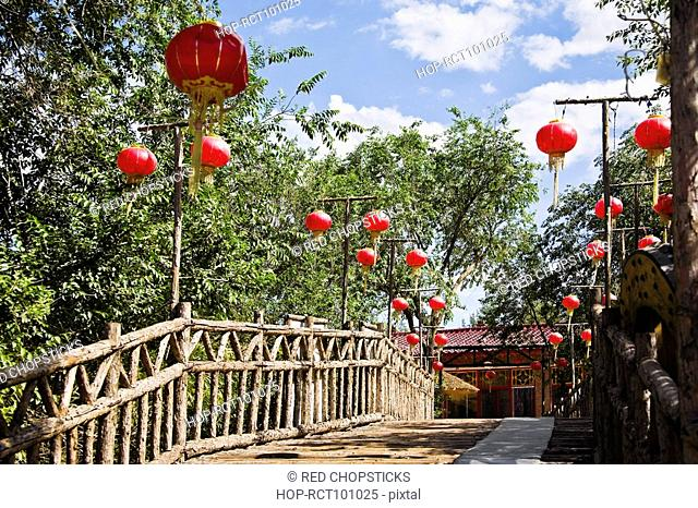 Low angle view of Chinese lanterns hanging on both sides of a footbridge, HohHot, Inner Mongolia, China