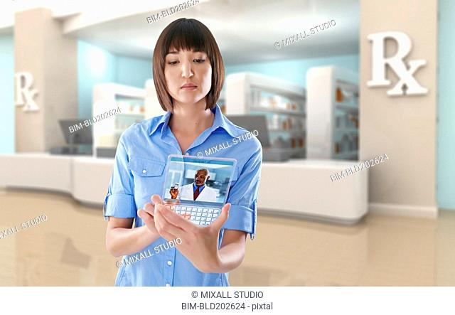 Mixed race woman using digital tablet in pharmacy