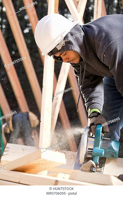 Carpenter using a circular saw for cutting rafter