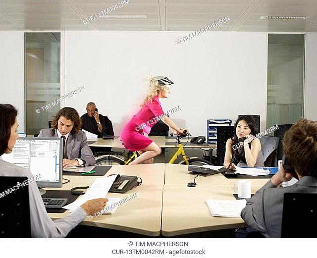 A girl cycles through an office