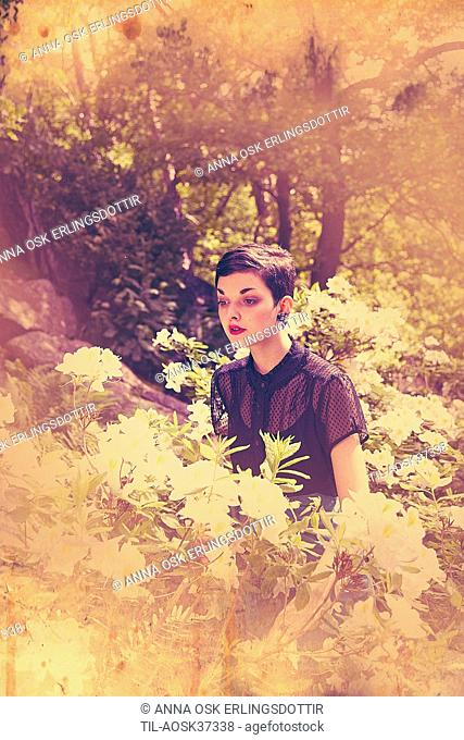 Lone female figure with short black hair in garden in summer