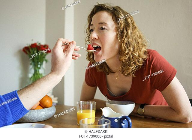 Hand of man feeding strawberry to woman at table in room