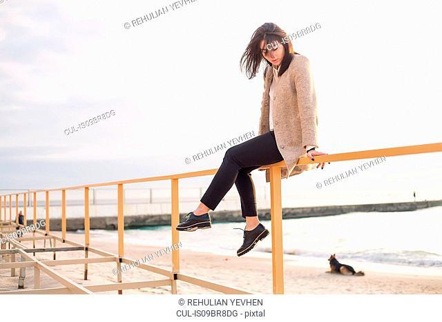 Woman sitting on handrail at beach
