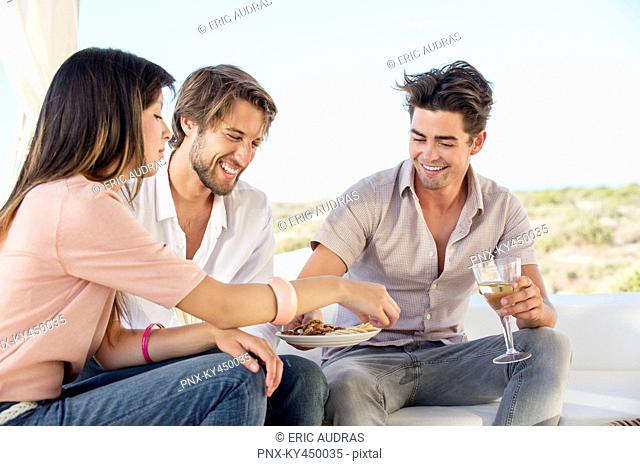 Three friends enjoying snacks and drinks in outdoor