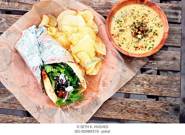 Meal of salad wrap, potato chips and dip