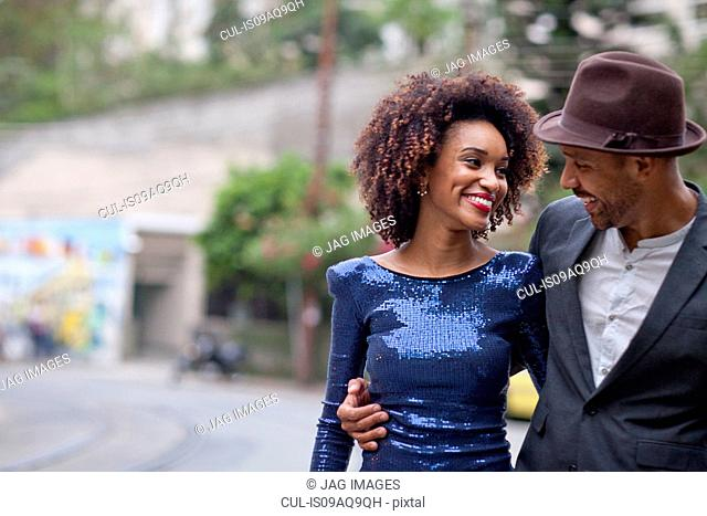 Couple walking along street together, smiling