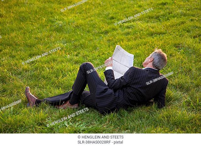 Businessman reading newspaper in grass