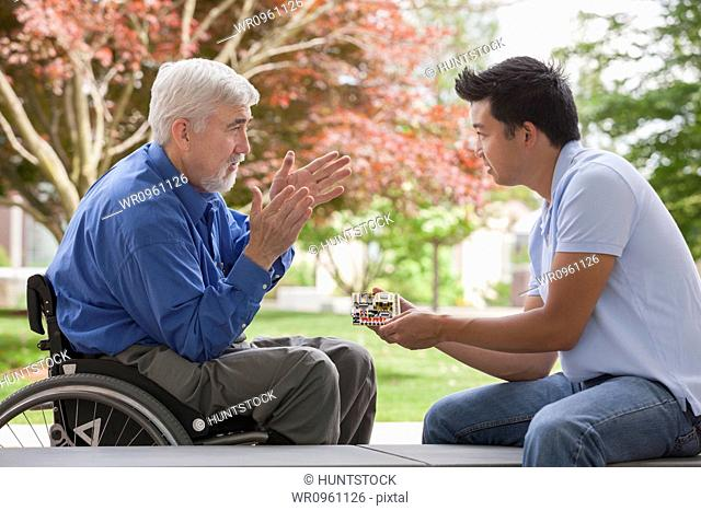 Engineer with muscular dystrophy and diabetes in his wheelchair talking with design engineer about microchips on circuit board