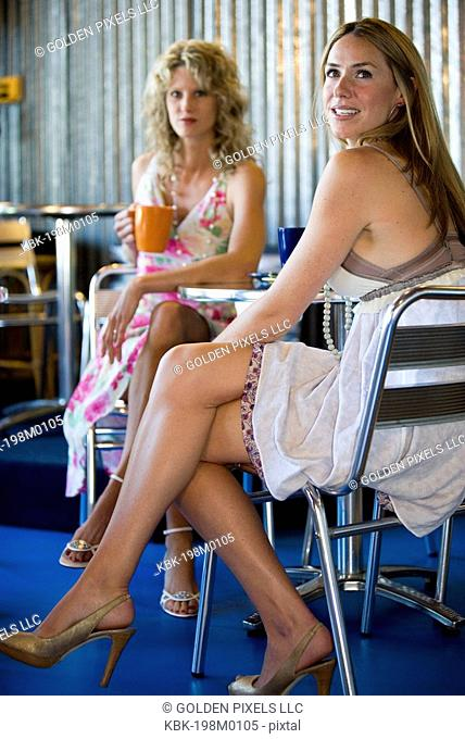 Two young women drinking coffee in a cafi