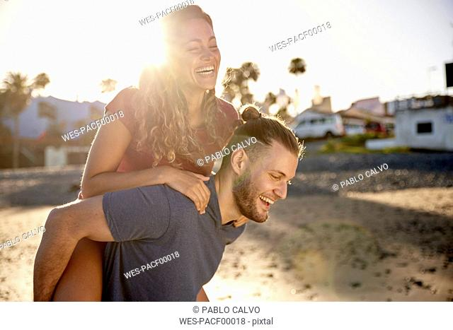 Young man giving his girlfriend a piggyback ride on the beach