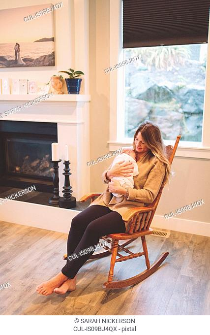 Mother sitting in rocking chair holding newborn baby boy
