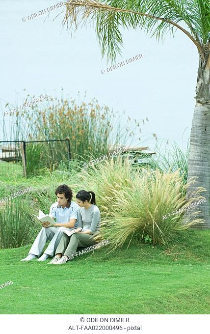 Couple sitting on grass, reading books