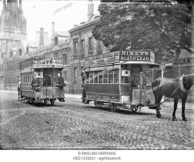 Two horse-drawn trams, High Street, Oxford, Oxfordshire, c1905. Two horse-drawn trams passing in the street with advertising panels attached to the roofs