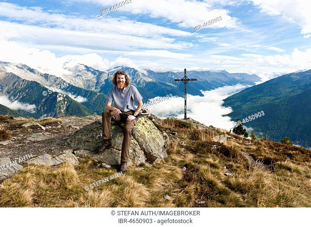 Hiker, hiker sits on rocks, Kleiner Nock (2227 m) with cross, Speikboden, view into the Ahrntal, at Sand in Taufers, Campo Tures, Ahrntal, Valle Aurina