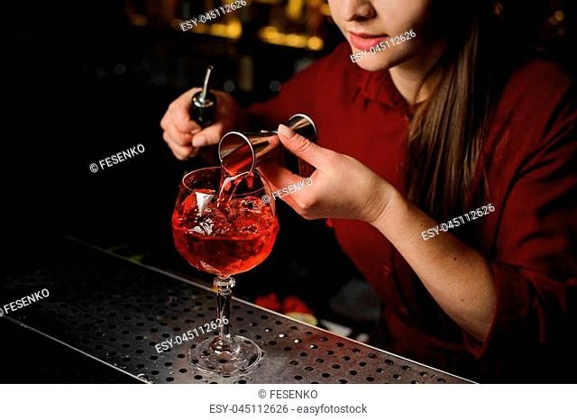 Woman bartender pouring bitter into a glass for making a fresh and tasty Aperol syringe cocktail on the bar counter