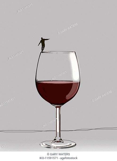 Man balancing precariously on rim of large wine glass