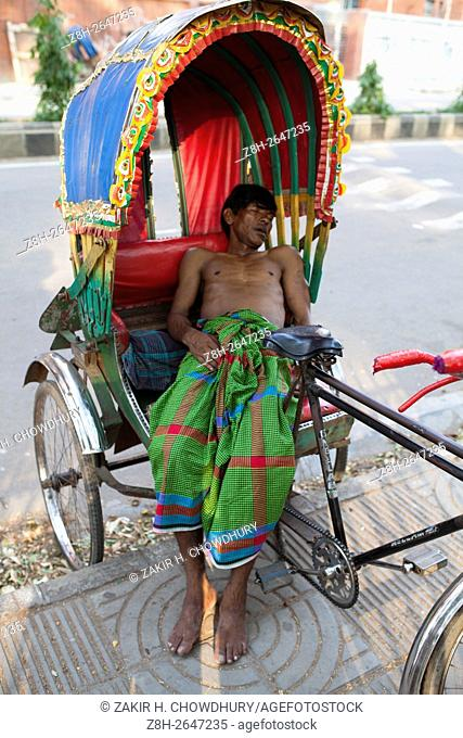 DHAKA, BANGLADESH - APRIL 15 : Exhausted by the scorching summer heat rickshaw pullers sleep under trees on their rickshaw beside the streets in the afternoon...