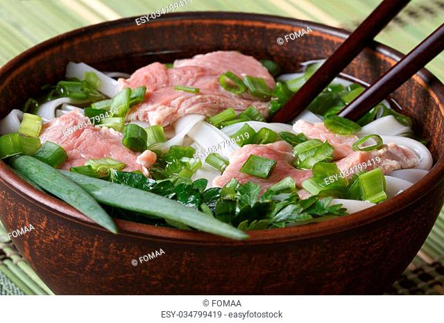 Asian soup with beef, rice noodles and fresh herbs in a bowl. Close-up of a horizontal