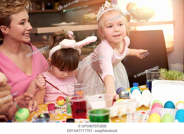 Girls focused on painting easter eggs
