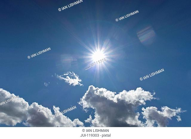 Blue sky with fluffy white clouds and sunburst