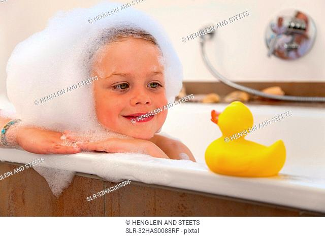 Boy covered in bubbles in bathtub