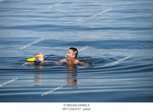 A young Caucasian girl swims with her dad in Seneca Lake, upstate New York; Dresden, New York, United States of America